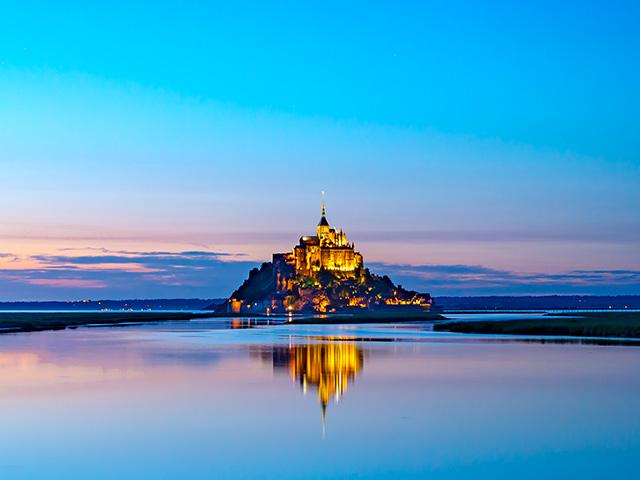 モンサンミッシェルは陸地から約2km離れたサン・マロ湾に浮かぶ孤島の上に建っているフランスの修道院です。朝焼けや夕焼けに照らされるモンサンミッシェルの神秘的な美しさは、世界中の観光客を魅了し続けています。